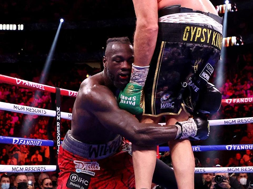 Deontay Wilder holds on after being dropped by Tyson Fury (Getty)