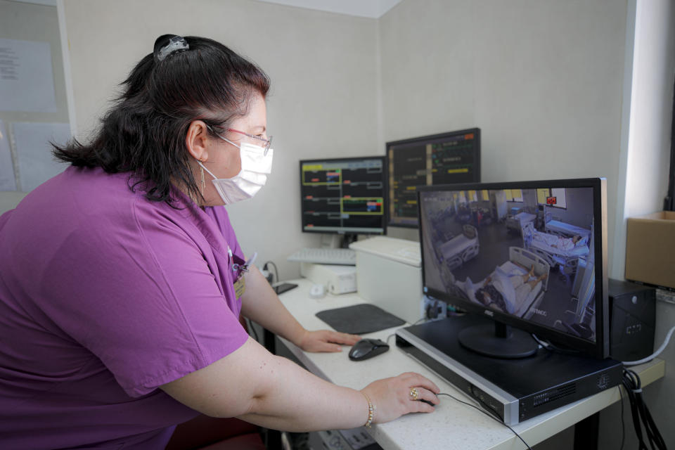 Medical staff monitor COVID-19 patients, at the Colentina Hospital in Bucharest, Romania, Thursday, Feb. 25, 2021. A year ago, Romania reported its first case of COVID-19, prompting the country's strapped medical system to turn its focus to treating COVID-19 patients. As a result, many patients with other conditions — including HIV but also cancer and other illnesses — have either been denied critical care or stopped going to their regular appointments, fearful of becoming infected.(AP Photo/Vadim Ghirda)