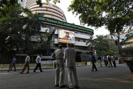 People watch a large screen displaying India's benchmark share index on the facade of BSE building in Mumbai