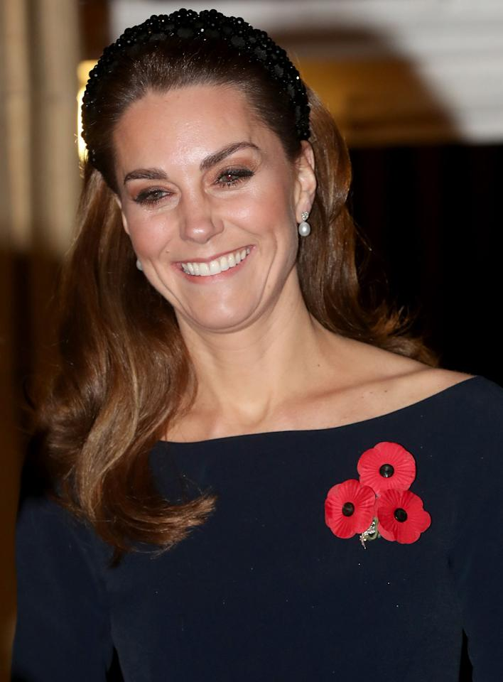 """Meghan and Kate opted for similar looks for the occasion, both wearing black dresses adorned with a <a href=""""https://people.com/royals/why-the-royal-family-wears-red-poppy-pins-and-what-it-signifies/"""">red poppy pin</a>, an artificial flower that has been used since 1921 to commemorate military members who have died in war."""