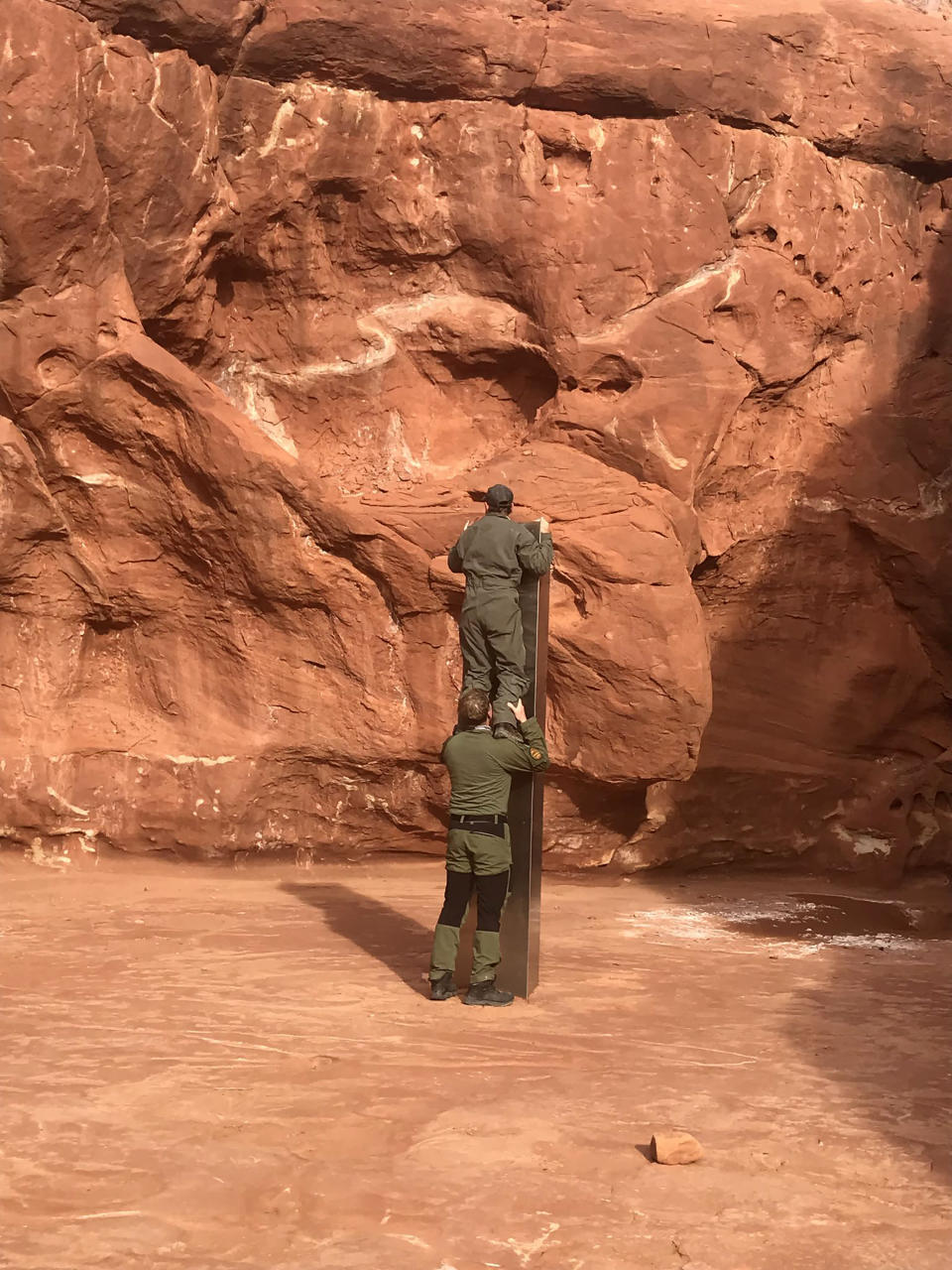 This Nov. 18, 2020 photo provided by the Utah Department of Public Safety shows Utah state workers checking out a metal monolith that was found installed in the ground in a remote area of red rock in Utah. The smooth, tall structure was found during a helicopter survey of bighorn sheep in southeastern Utah, officials said Monday. State workers from the Utah Department of Public Safety and Division of Wildlife Resources spotted the gleaming object from the air and landed nearby to check it out. The exact location is so remote that officials are not revealing it publicly, worried that people might get lost or stranded trying to find it and need to be rescued. (Utah Department of Public Safety via AP)