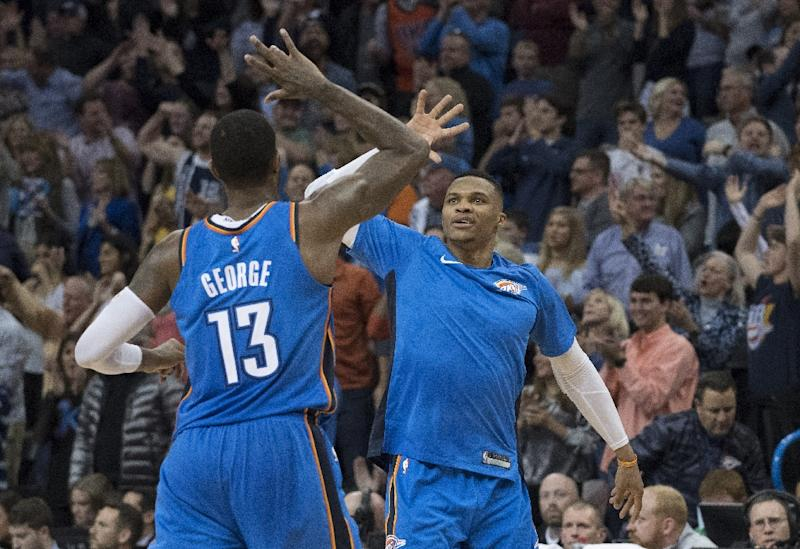 Paul George and Russell Westbrook of the Oklahoma City Thunder celebrate during the second half of their NBA game against the Golden State Warriors, at the Chesapeake Energy Arena in Oklahoma City, on November 22, 2017 (AFP Photo/J Pat Carter)
