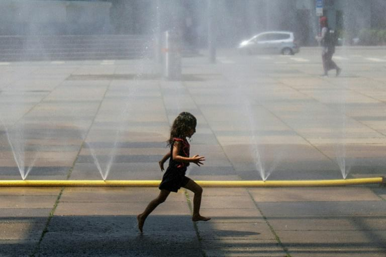 A girl runs through water at Praterstern Square in Vienna on July 25 amid a blistering heat wave (AFP Photo/ALEX HALADA)