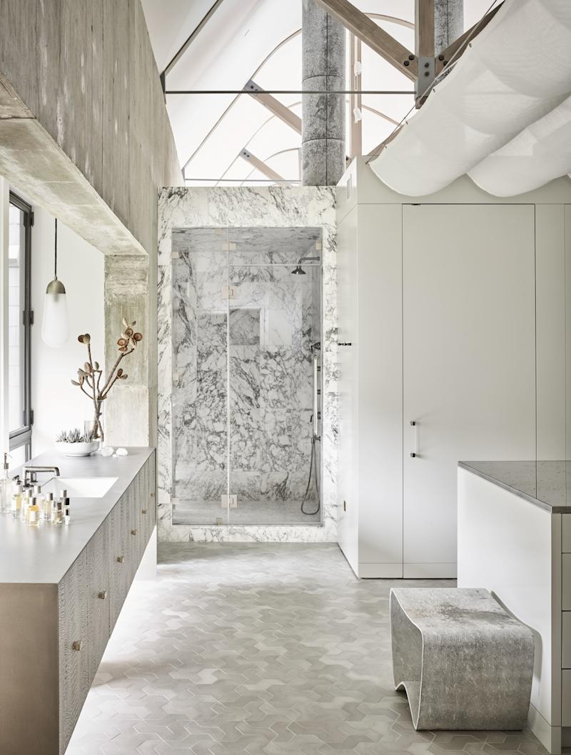 """Arabescato marble and cement tiles play off the poured concrete walls in the master bath, where there is purposely only one sink. """"It's just me, so why would I have two,"""" says McFayden. The island countertop is antiqued mirror framed with stainless steel."""