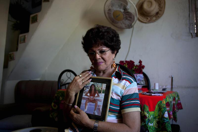 In this picture taken Aug. 2, 2012, Emelia Moreno, 75, a divorced, retired cashier, poses with a portrait of her only child, in Havana, Cuba. Moreno, whose daughter left for the United States a decade ago, knows that one day she'll be completely dependent on a Cuban government that is finding it ever harder to care for its burgeoning population of elderly. (AP Photo/Ramon Espinosa)