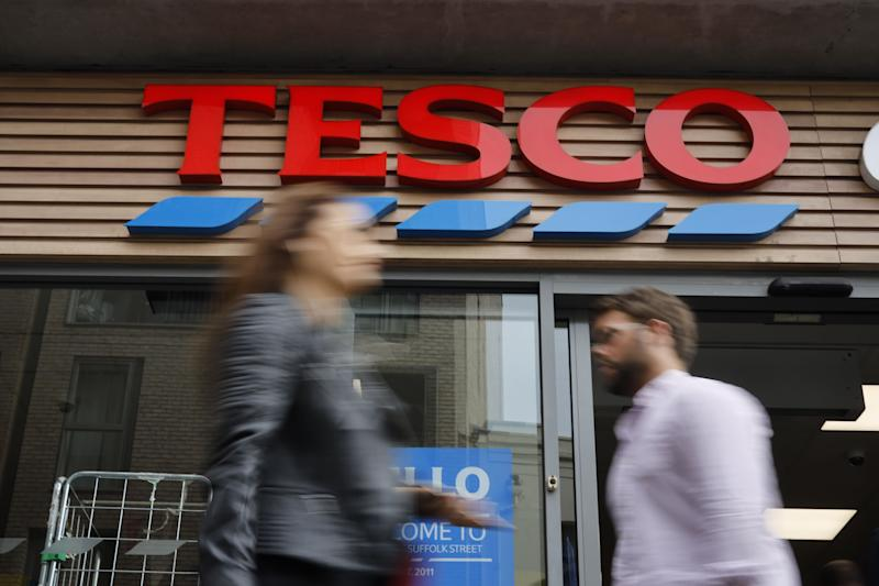 People walk past at a Tesco Express in central London on September 30, 2019. - Tesco, the Britain's biggest food retailer, will report its first-half results on October 2. (Photo by Tolga AKMEN / AFP) (Photo by TOLGA AKMEN/AFP via Getty Images)