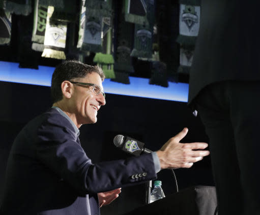 Seattle Sounders majority owner Adrian Hanauer talks to reporters, Tuesday, Aug. 13, 2019, in Seattle. Hanauer said Tuesday that the MLS soccer team is adding Seattle Seahawks NFL football quarterback Russell Wilson and his wife Ciara, hip-hop artist Macklemore, and Microsoft CEO Satya Nadella to the MLS club's ownership group, along with other investors. Hollywood producer Joe Roth, who helped bring the MLS to Seattle, is leaving the franchise. (AP Photo/Ted S. Warren)
