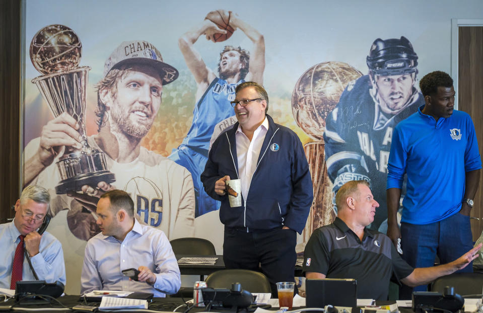 """FILE - Dallas Mavericks President Donnie Nelson, center, joins, from left, assistant general manager Keith Grant, director of scouting Jason White, director of player personnel Tony Ronzone and vice president of basketball operations Michael Finley, in Dallas, before the NBA basketball draft got underway in New York, in this Thursday, June 20, 2019, file photo. Mavericks general manager Donnie Nelson, instrumental in the club's acquisitions of Dirk Nowitzki and Luka Doncic, is leaving the organization after 24 seasons. The Mavericks said Wednesday, June 16, 2021, the club and Nelson agreed to part ways, with owner Mark Cuban saying the son of former coach Don Nelson was """"instrumental to our success and helped bring a championship to Dallas.""""(Smiley N. Pool/The Dallas Morning News via AP, File)"""