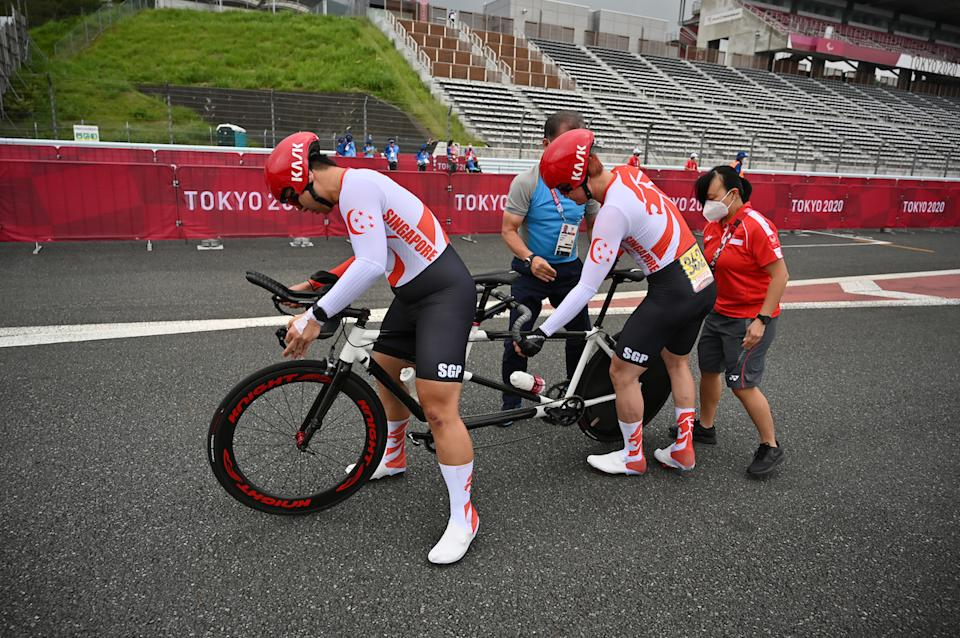 Singapore cyclists Ang Kee Meng (left) and Steve Tee stop for a technical problem in the men's time trial road cycling event at the 2020 Tokyo Paralympics. (PHOTO: Sport Singapore)