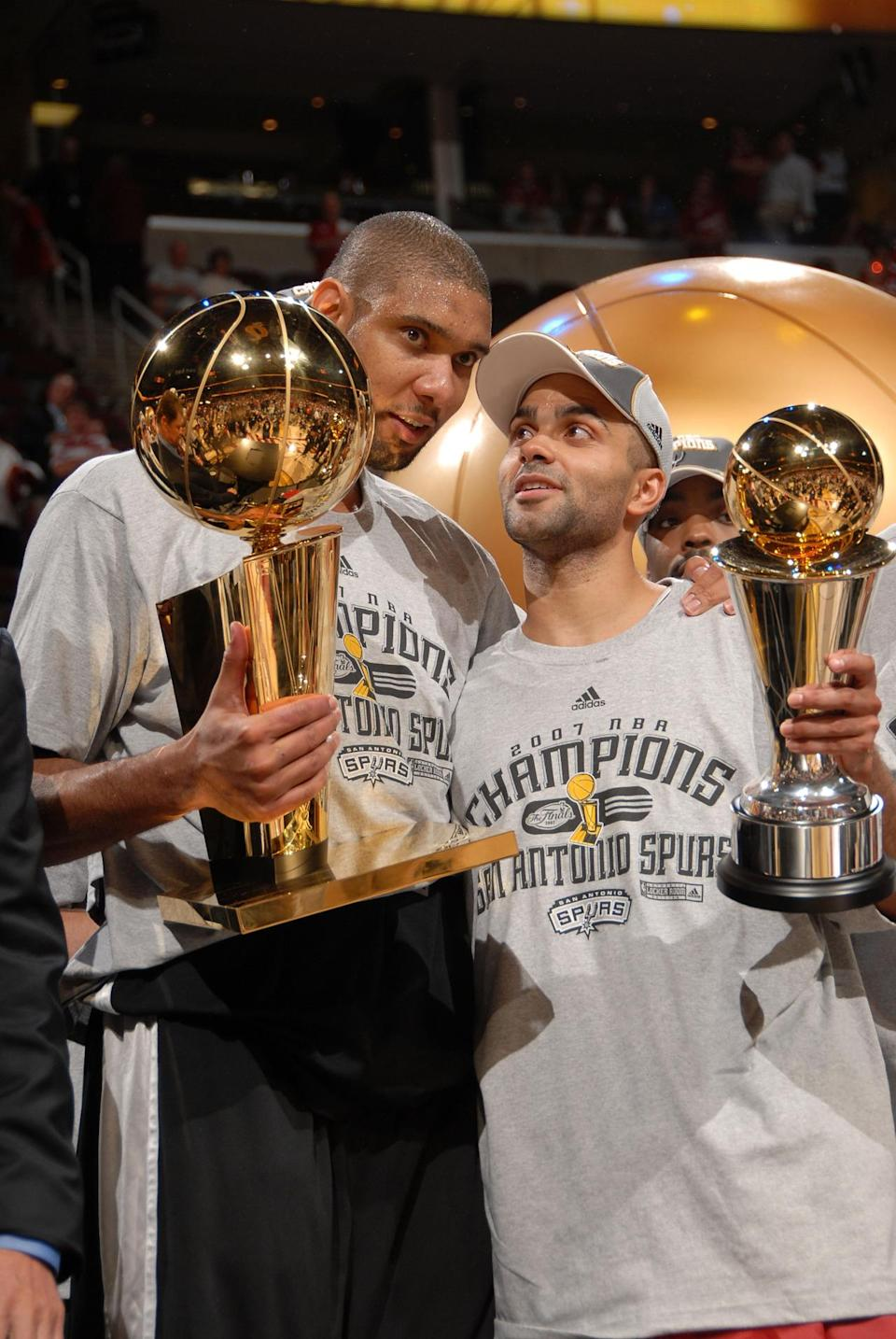 <p>2007: Tim Duncan #21 and Finals MVP Tony Parker #9 of the San Antonio Spurs celebrate with the Larry O'Brien Trophy and MVP Trophy after they won the NBA Championship with their 83-82 win against the Cleveland Cavaliers in Game Four of the NBA Finals at the Quicken Loans Arena on June 14, 2007 in Cleveland, Ohio.</p>