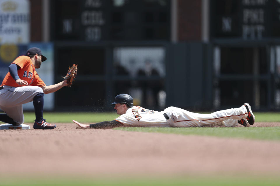 Houston Astros' Jose Altuve, left, tags out San Francisco Giants' Mike Yastrzemski on a runner's fielder's choice during the third inning of a baseball game in San Francisco, Saturday, July 31, 2021. (AP Photo/Jed Jacobsohn)