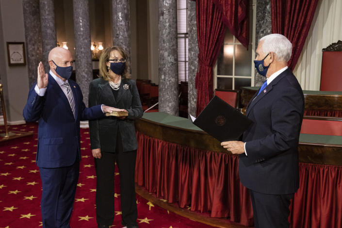 Sen. Mark Kelly, D-Ariz., with his wife former Rep. Gabby Giffords, D-Ariz., participates in a re-enactment of his swearing-in Wednesday, Dec. 2, 2020, by Vice President Mike Pence in the Old Senate Chamber on Capitol Hill in Washington. (Graeme Jennings/Pool via AP)