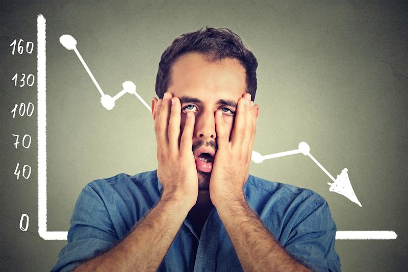 A man holding his face in his hands in front of a chart of a falling stock.