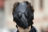 A man wears a mask as demonstrators gather to protest the COVID-19 preventative measures downtown Prague, Czech Republic, Wednesday, Oct. 28, 2020. Coronavirus infections in the Czech Republic have again jumped to record levels amid new restrictive measures imposed by the government to curb the spread. (AP Photo/Petr David Josek)