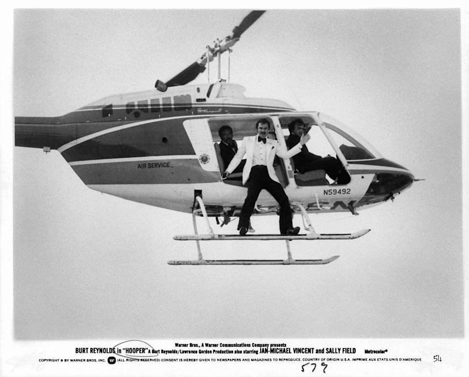 <p>Burt Reynolds shoots a daring scene on a helicopter for his movie <em>Hooper</em> in 1978. The film was the actor's follow-up to <em>Smokey and the Bandit. </em></p>