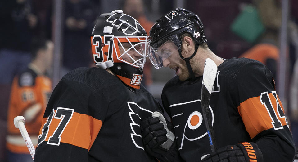 Philadelphia Flyers' Brian Elliott, left, celebrates the win with Sean Couturier, right, following the third period of an NHL hockey game against the Chicago Blackhawks, Saturday, Nov. 10, 2018, in Philadelphia. The Flyers won 4-0. (AP Photo/Chris Szagola)