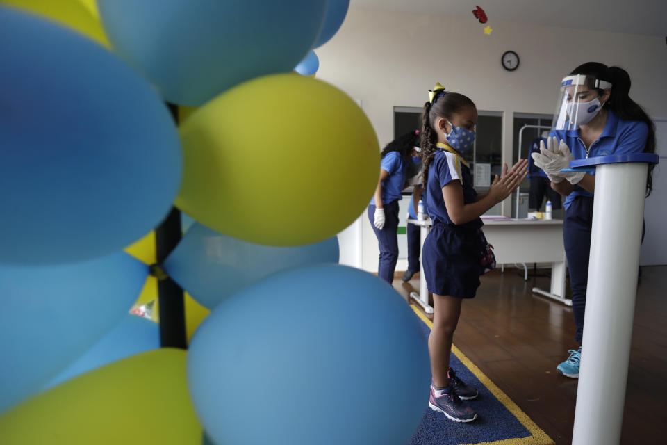 A student wearing a mask to curb the spread of the new coronavirus is given instructions on hand hygiene as she arrives for class at a private school in Brasilia, Brazil, Monday, Sept. 21, 2020. Private schools, closed since the second half of March due to the COVID-19 pandemic, have reopened their doors. Returning to school is optional and online classes continue for students who choose to stay at home watching classes via remote education. (AP Photo/Eraldo Peres)
