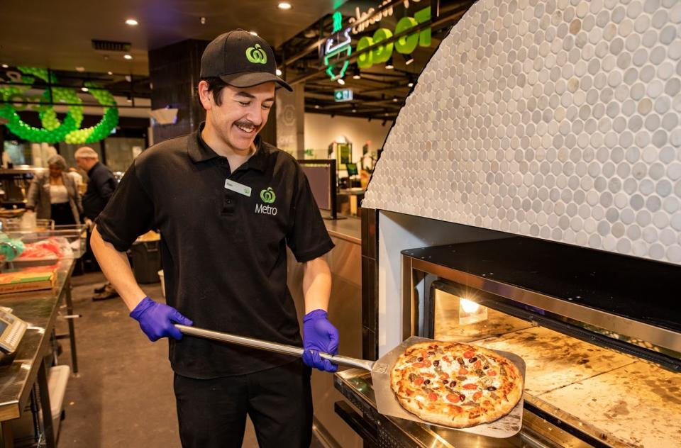 A Woolworths supermarket worker holds pizza fresh out of the oven.