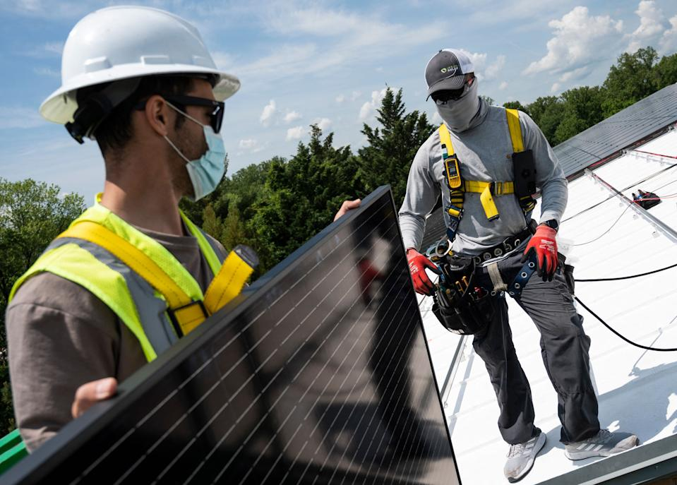 Employees with Ipsun Solar unload solar panels on the roof of the Peace Lutheran Church in Alexandria, Virginia on May 17, 2021. (Photo by Andrew CABALLERO-REYNOLDS/AFP)