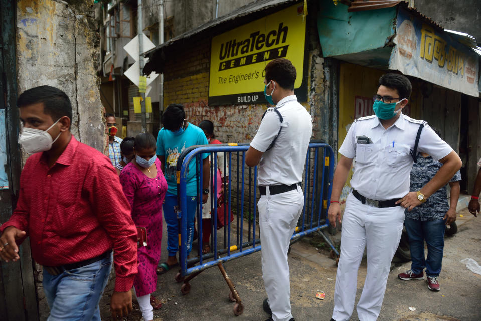 People move in and out of the containment area before the lockdown.Coronavirus has affected a huge number of people in Kolkata daily, so to curb the spread of coronavirus pandemic the government has identified some areas with high number of cases and imposed complete lockdown for 7 days in this selected containment areas in Kolkata where no one can go out or go in Police personnel will provide essential items to the residents. (Photo by Sumit Sanyal/SOPA Images/LightRocket via Getty Images)
