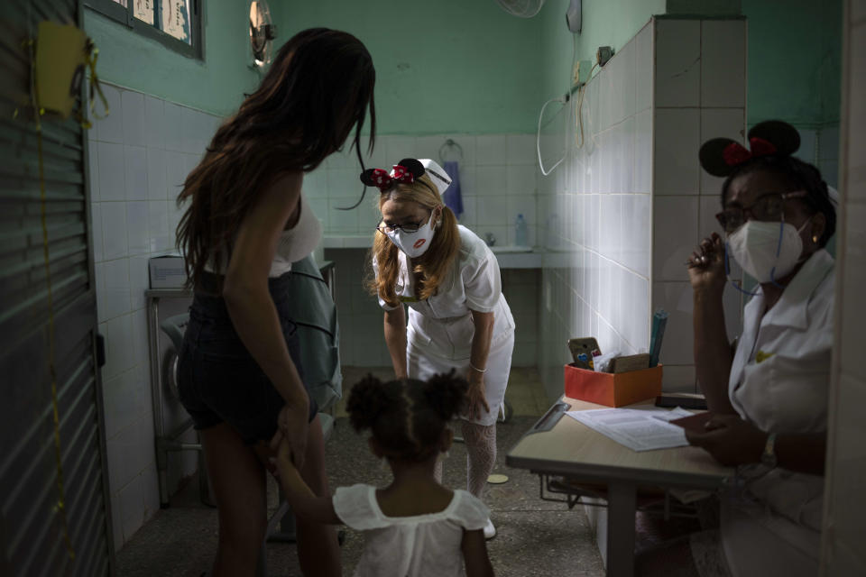 A nurse greets a young girl as she arrives with her mother to receive a dose of the Soberana-02 COVID-19 vaccine, in Havana, Cuba, Thursday, Sept. 16, 2021. Cuba began inoculating children as young as 2-years-old with locally developed vaccines on Thursday.(AP Photo/Ramon Espinosa)
