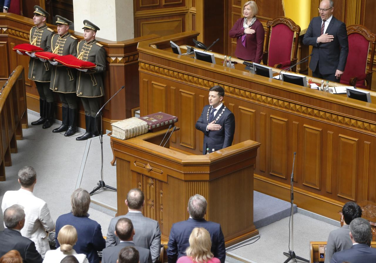 Ukrainian new President Volodymyr Zelenskiy, center, sings the national anthem during his inauguration ceremony in Kiev, Ukraine, Monday, May 20, 2019. Television star Volodymyr Zelenskiy has been sworn in as Ukraine's next president after he beat the incumbent at the polls last month. The ceremony was held at Ukrainian parliament in Kiev on Monday morning. (AP Photo/Efrem Lukatsky)