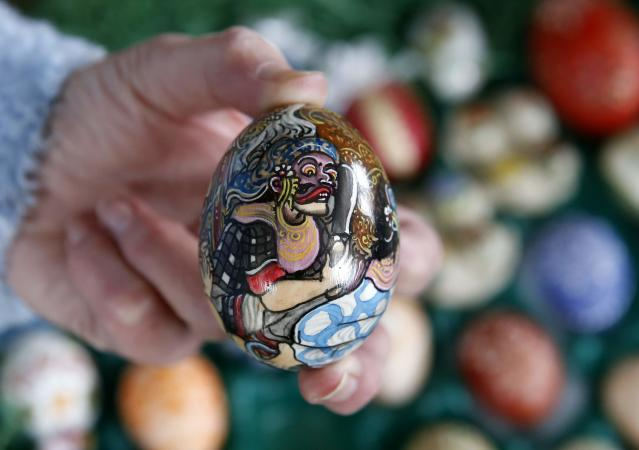 German pensioner Christa Kraft displays a colourful hand-painted Easter egg before she decorates an apple tree in the garden of her summerhouse, in the eastern German town of Saalfeld, March 19, 2014. Each year since 1965 Volker and his wife Christa spend up to two weeks decorating the apple tree with their collection of 10,000 colourful hand-painted Easter eggs in time for Easter celebrations. REUTERS/Fabrizio Bensch (GERMANY - Tags: SOCIETY RELIGION)