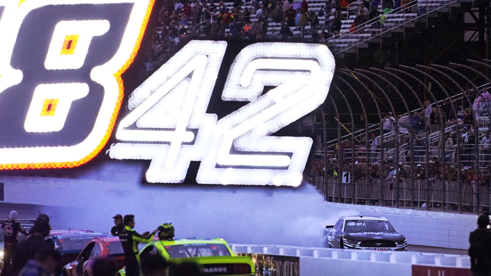 Aric Almirola does a burnout at dusk while celebrating his win in the NASCAR Cup Series auto race Sunday, July 18, 2021, in Loudon, N.H. (AP Photo/Charles Krupa)