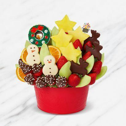 """<p><strong>Edible Arrangements </strong></p><p>ediblearrangements.com</p><p><strong>$74.99</strong></p><p><a href=""""https://go.redirectingat.com?id=74968X1596630&url=https%3A%2F%2Fwww.ediblearrangements.com%2Ffruit-gifts%2Fholly-jolly-village-6193%3Ft%3D1600722464145%26ArrangementGroupID%3D281&sref=https%3A%2F%2Fwww.goodhousekeeping.com%2Fholidays%2Fgift-ideas%2Fg34054234%2Fbest-gift-baskets-for-women%2F"""" rel=""""nofollow noopener"""" target=""""_blank"""" data-ylk=""""slk:Shop Now"""" class=""""link rapid-noclick-resp"""">Shop Now</a></p><p>A fun twist on the traditional fruit basket, this cheery arrangement has reindeer-shaped pineapple covered in chocolate pineapple, citrus slices, delicious berries, melon, and much more. </p>"""