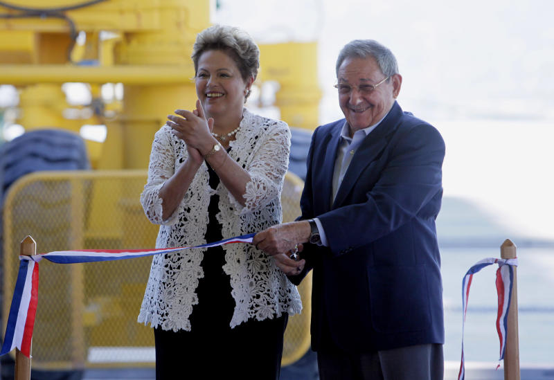 """Brazil's President Dilma Rousseff, left, and Cuba's President Raul Castro cut the ribbonBrazil's President Dilma Rousseff, left, and Cuba's President Raul Castro make a tour by bus after the inauguration ceremony of the first phase of a port overhaul project in Mariel, Cuba, Monday, Jan. 27, 2014. The new port will be able to accommodate deeper-drafting """"post-Panamax"""" ships that will begin crossing the Panama Canal once an expansion project there is completed in the next year or so.(AP Photo/Ismael Francisco, Cubadebate)"""