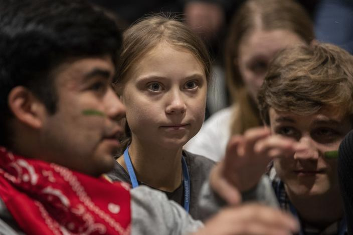 Climate activist Greta Thunberg, center, talks with other climate activists youth at the COP25 climate talks summit in Madrid, Friday Dec. 6, 2019. Thunberg arrived in Madrid Friday to join thousands of other young people in a march to demand world leaders take real action against climate change. (AP Photo/Bernat Armangue)