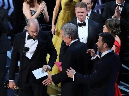 Brian Cullinan and Martha Ruiz  of PricewaterhouseCoopers stand on stage behind presenter Warren Beatty during presentation of Best Picture category at 89th Academy Awards