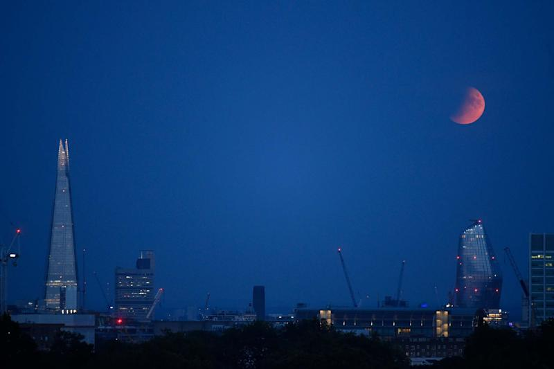 A partial lunar eclipse appears over the London skyline (Getty Images)