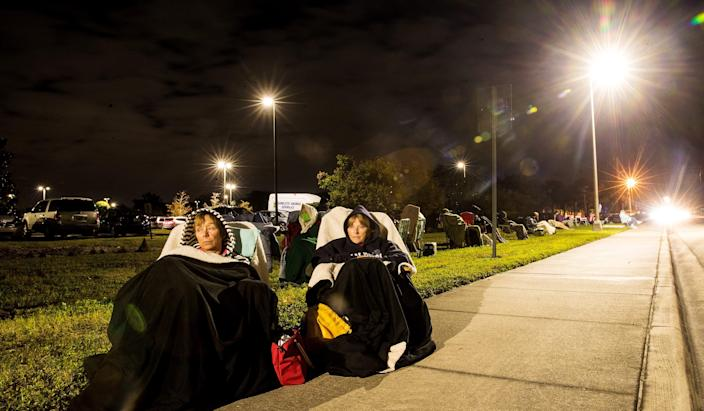 Terri Kado, 66, right, and Patty Tubbs, 68, friends from Fort Myers Beach, Florida, wait in line for a COVID-19 vaccine in the early morning hours of Dec. 30 at Lakes Park Regional Library.
