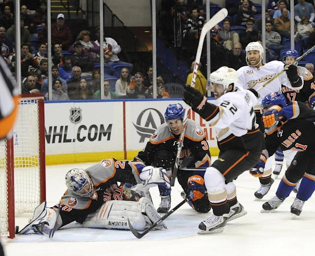 New York Islanders goalie Evgeni Nabokov (20) dives unsuccessfully to block a shot on goal by Anaheim Ducks' Mathieu Perreault (22) as Islanders' Travis Hamonic (3) tries to defend during the third period of an NHL hockey game on Saturday, Dec. 21, 2013, in Uniondale, N.Y. The Ducks won 5-3. (AP Photo/Kathy Kmonicek)