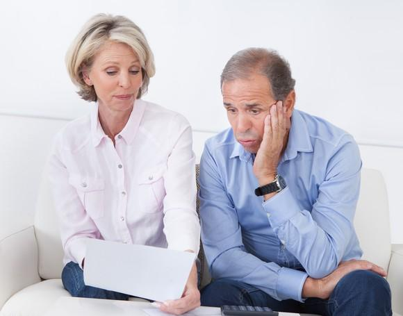 Worried-looking man and woman examining a piece of paper.