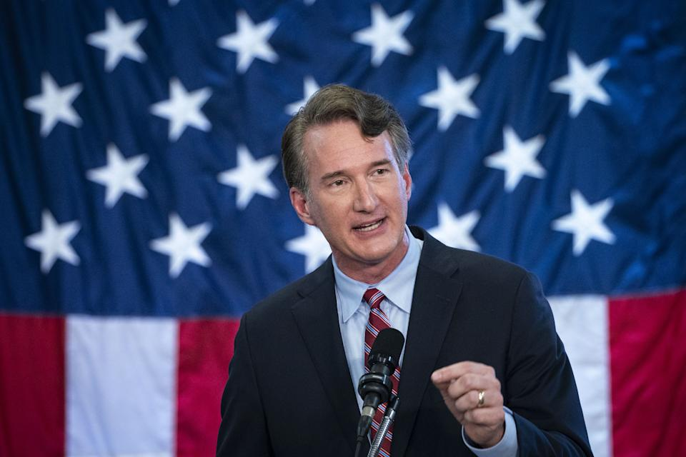 Glenn Youngkin speaks before a microphone in front of an American flag.