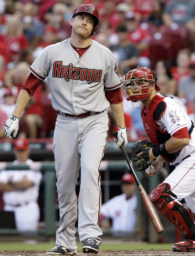 Arizona Diamondbacks' Mark Trumbo strikes out against Cincinnati Reds starting pitcher Mike Leake in the fourth inning of a baseball game, Tuesday, July 29, 2014, in Cincinnati. Devin Mesoraco catches at right. (AP Photo/Al Behrman)