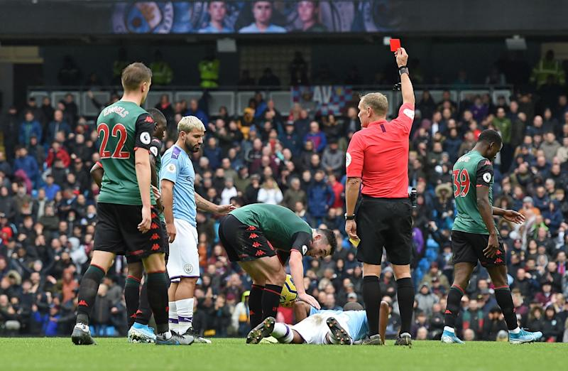 Referee Graham Scott shows the a red card to send off Manchester City's Brazilian midfielder Fernandinho (bottom) during the English Premier League football match between Manchester City and Aston Villa at the Etihad Stadium in Manchester, north west England, on October 26, 2019. - Manchester City won the game 3-0. (Photo by Paul ELLIS / AFP) / RESTRICTED TO EDITORIAL USE. No use with unauthorized audio, video, data, fixture lists, club/league logos or 'live' services. Online in-match use limited to 120 images. An additional 40 images may be used in extra time. No video emulation. Social media in-match use limited to 120 images. An additional 40 images may be used in extra time. No use in betting publications, games or single club/league/player publications. / (Photo by PAUL ELLIS/AFP via Getty Images)
