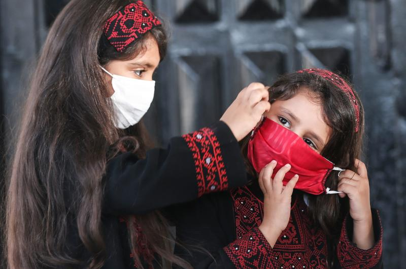 Palestinian girls wearing protective masks attend a graduation ceremony from the Police Academy amid concerns about the spread of the coronavirus COVID-19 in Gaza City on May 7, 2020. (Photo by MAHMUD HAMS / AFP) (Photo by MAHMUD HAMS/AFP via Getty Images)