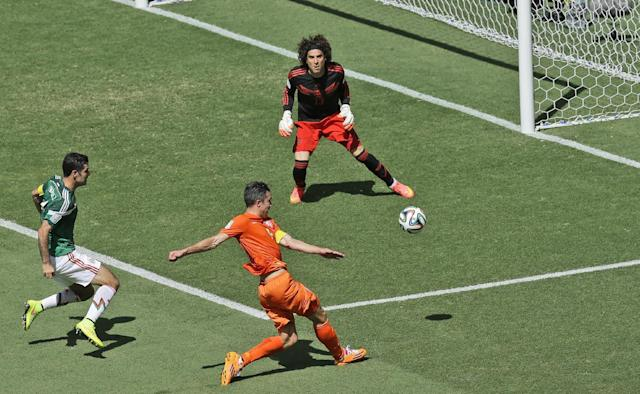 Netherlands' Robin van Persie, front, shoots past the goal of Mexico's goalkeeper Guillermo Ochoa during the World Cup round of 16 soccer match between the Netherlands and Mexico at the Arena Castelao in Fortaleza, Brazil, Sunday, June 29, 2014. (AP Photo/Themba Hadebe)