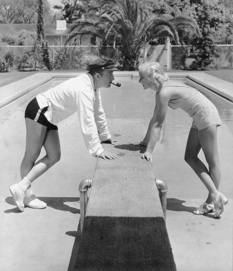 <p>Bing Crosby and his wife Dixie Lee come face to face as they lean on the diving board of their swimming pool in Rancho Santa Fe in 1935. </p>