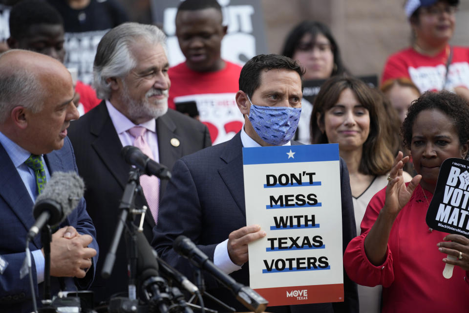 Rep. Trey Martinez Fischer, D-San Antonio, holds a sign as he and other Democratic caucus members join a rally on the steps of the Texas Capitol to support voting rights, Thursday, July 8, 2021, in Austin, Texas. (AP Photo/Eric Gay)