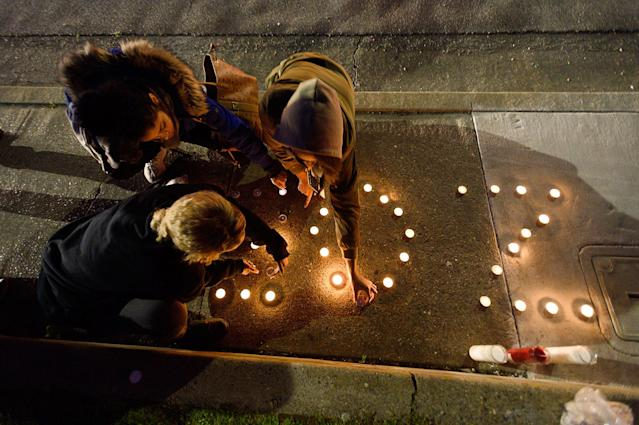 "<p>Amauria Hawkins, right, lights candles spelling out ""ZOE,"" the nickname of their friend Stephon Clark, during a candlelight vigil for Clark at the intersection of Florin and 29th Street on Friday, March 23, 2018 in Sacramento, Calif. (Photo: Paul Kitagaki Jr./Sacramento Bee via ZUMA Wire) </p>"