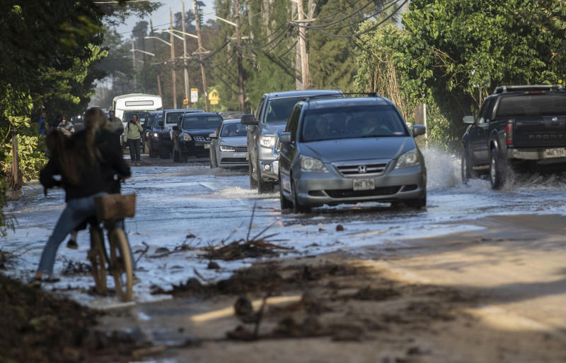 FILE - In this Feb. 10, 2019 file photo, vehicles pass through surf that washed over a roadway on Oahu's north shore near Haleiwa, Hawaii. Some of Hawaii's most iconic beaches could soon be underwater as rising sea levels caused by global warming overtake its white sand beaches and bustling city streets. That's alarming for a state where beach tourism is the primary economic driver. (Cindy Ellen Russel/Honolulu Star-Advertiser via AP, file)
