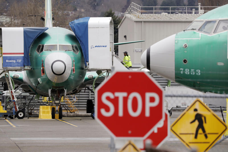 Boeing 737 MAX jets sit parked Monday, Dec. 16, 2019, in Renton, Wash. Boeing Co. will temporarily stop producing its grounded 737 MAX jet starting in January as it struggles to get approval from regulators to put the plane back in the air. The company says it will halt production at the plant with 12,000 employees in Renton, near Seattle. (AP Photo/Elaine Thompson)