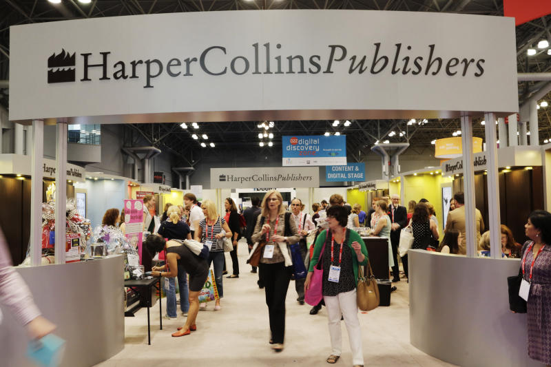 FILE - This May 28, 2015 file photo shows attendees at the HarperCollins Publishers booth during BookExpo America in New York. Publishing's annual national convention, BookExpo, has been postponed until July. Organizers cited concerns about the coronavirus in rescheduling the gathering, originally scheduled to take place in late May at the Jacob Javits Convention Center in Manhattan. (AP Photo/Mark Lennihan, File)