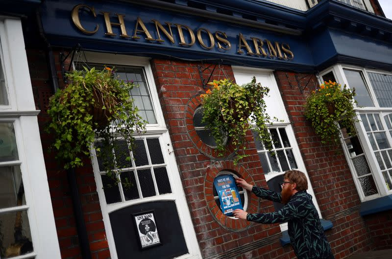 Landlord Are Kolltveit pins a safety sign to a window of the Chandos Arms pub ahead of pubs reopening following the coronavirus disease (COVID-19) outbreak, in London