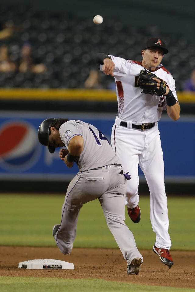Arizona Diamondbacks shortstop Nick Ahmed turns the double play while avoiding Colorado Rockies' Tony Wolters (14) in the eighth inning during a baseball game, Monday, Aug. 19, 2019, in Phoenix. (AP Photo/Rick Scuteri)