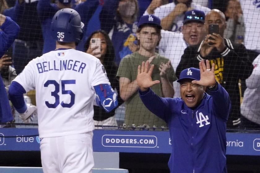 Los Angeles Dodgers' Cody Bellinger, left, celebrates with manager Dave Roberts after hitting a solo home run during the eighth inning of a baseball game against the San Diego Padres Wednesday, Sept. 29, 2021, in Los Angeles. (AP Photo/Mark J. Terrill)